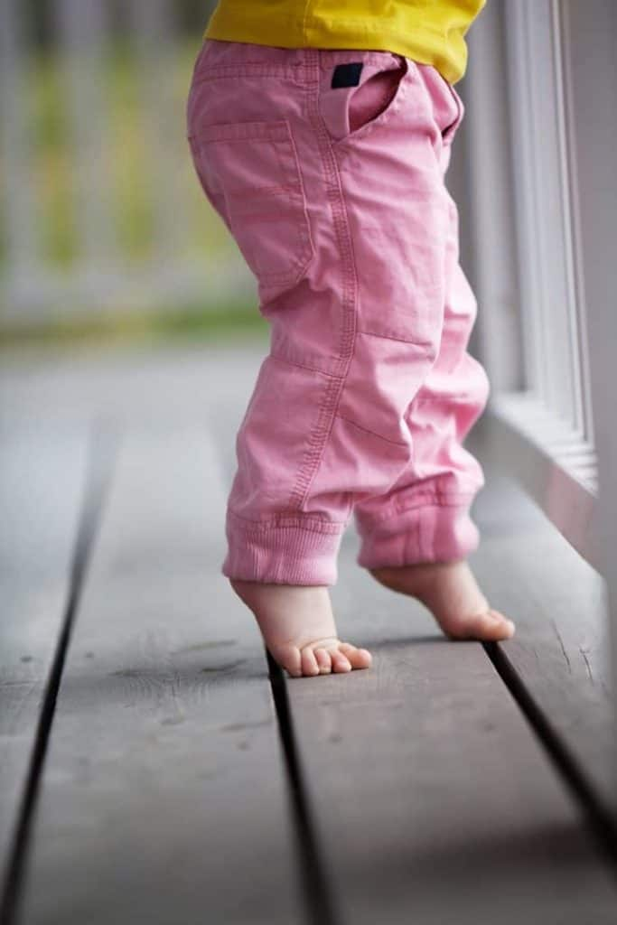 Toddler standing on tiptoes on a wooden deck