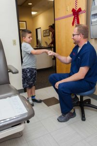 dr mikkel jarman with kid patient