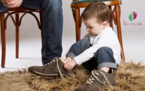 child putting on dad's shoes